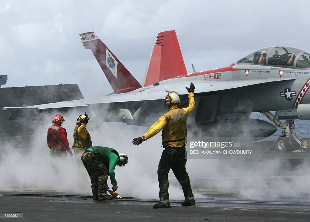 US naval crew-members signal as a fighter aircraft prepares to take-off from the US super-carrier USS Kitty Hawk in the Bay of Bengal, during the Malabar exercise, 07 September 2007. Twenty-seven ships and submarines from the United States, Australia, Japan and Singapore have joined seven from host India off the Andamans archipelago in the Bay of Bengal for six-day manoeuvres in the international exercises, codenamed Malabar, which started on the 04 September. AFP PHOTO/Deshakalyan CHOWDHURY