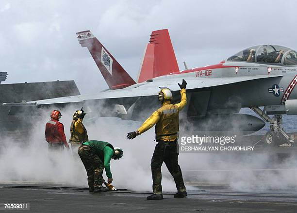 US naval crewmembers signal as a fighter aircraft prepares to takeoff from the US supercarrier USS Kitty Hawk in the Bay of Bengal during the Malabar...