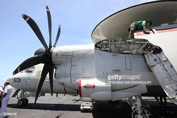 A US naval officer checks a fighter craft before take off on the US supercarrier USS Kitty Hawk in the Bay of Bengal during the Malabar exercise 07...