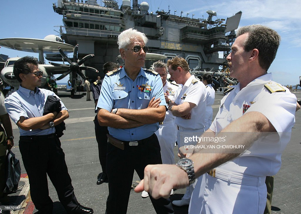 US naval officer Rick Wren (R) shares his experiences with his Indian counter part on the US super-carrier USS Kitty Hawk in the Bay of Bengal, during the Malabar exercise, 07 September 2007. Twenty-seven ships and submarines from the United States, Australia, Japan and Singapore have joined seven from host India off the Andamans archipelago in the Bay of Bengal for six-day manoeuvres in the international exercises, codenamed Malabar, which started on the 04 September. AFP PHOTO/Deshakalyan CHOWDHURY