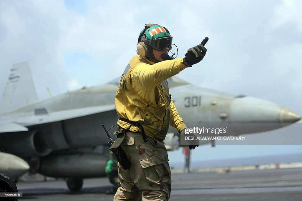 A US naval officer signals a fighter craft during take-off on the US super-carrier USS Kitty Hawk in the Bay of Bengal, during the Malabar exercise, 07 September 2007. Twenty-seven ships and submarines from the United States, Australia, Japan and Singapore have joined seven from host India off the Andamans archipelago in the Bay of Bengal for six-day manoeuvres in the international exercises, codenamed Malabar, which started on the 04 September. AFP PHOTO/Deshakalyan CHOWDHURY