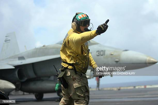 A US naval officer signals a fighter craft during takeoff on the US supercarrier USS Kitty Hawk in the Bay of Bengal during the Malabar exercise 07...