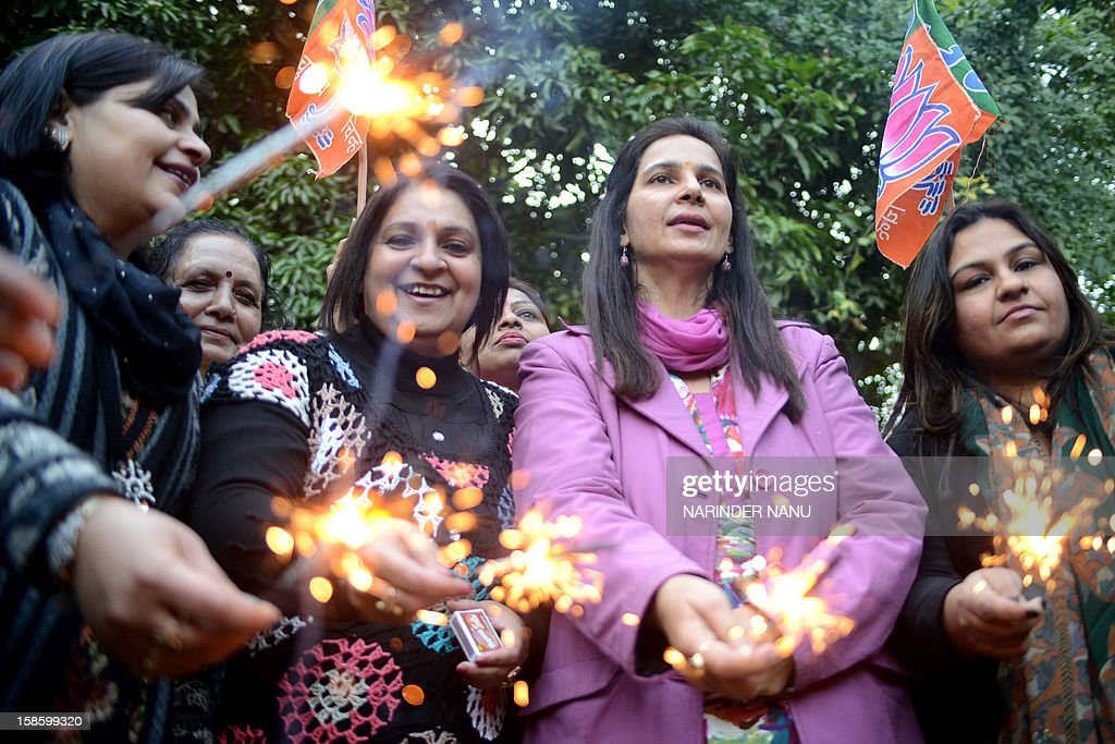 Navjot Kaur Sidhu (C) Indian Member of the Legislative Assembly (MLA) and wife of Former Indian cricketer and member of parliament Navjot Singh Sidhu, along with members of Bharatiya Janata Party (BJP) play with sparklers as they celebrate the assembly election results in Amritsar on December 20, 2012. Gujarat chief minster Narendra Modi is heading for a landslide election win in Gujarat on , firming up his chances of being nominated by the BJP for running for prime minister in 2014.AFP PHOTO/ NARINDER NANU
