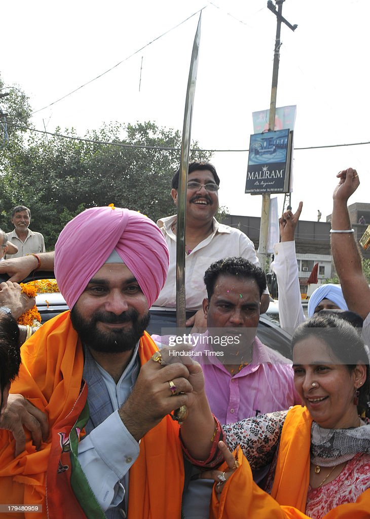 Navjot Kaur Sidhu (R ) wife of BJP MP from Amritsar Navjot Singh Sidhu present him a sword during his visit to his constituency after a long lap, on September 4, 2013 in Amritsar, India. In the long absenceof MP Sidhu from Amritsar his wife Navjot Kaur Sidhu defend him many times.