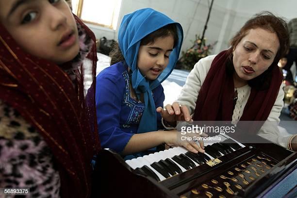 Navneeth Babra and Sahiba Babra get instruction on how to play the harmonium from Sahiba's mother Gulshan Babra at the new National Gurdwara or house...