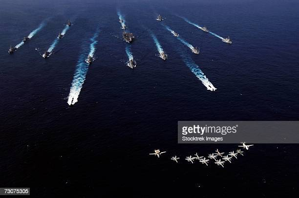 U.S. Navy aircraft from Carrier Air Wing Five fly over a formation of U.S. and Japanese ships in the Pacific Ocean November 14, 2006, at the conclusion of ANNUALEX 2006.