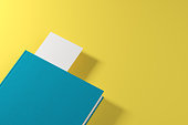 Closed green book with a white bookmark is lying on a yellow surface. Concept of advertising. 3d rendering mock up