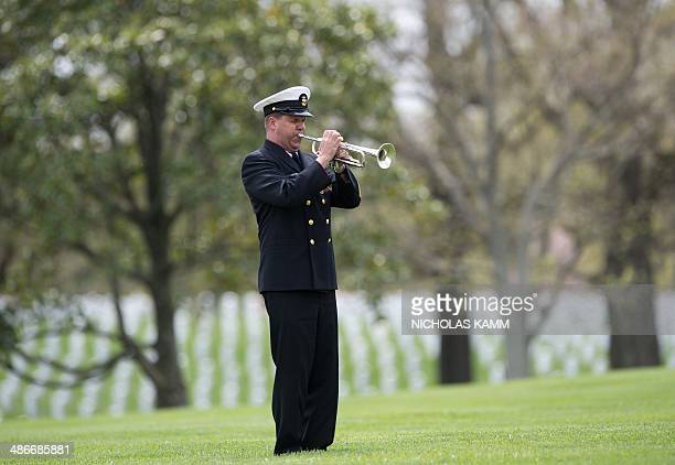 A Navy bugler plays taps during the funeral of slain US Navy MasteratArms 2nd Class Mark Mayo who was killed during a shooting incident at Naval...