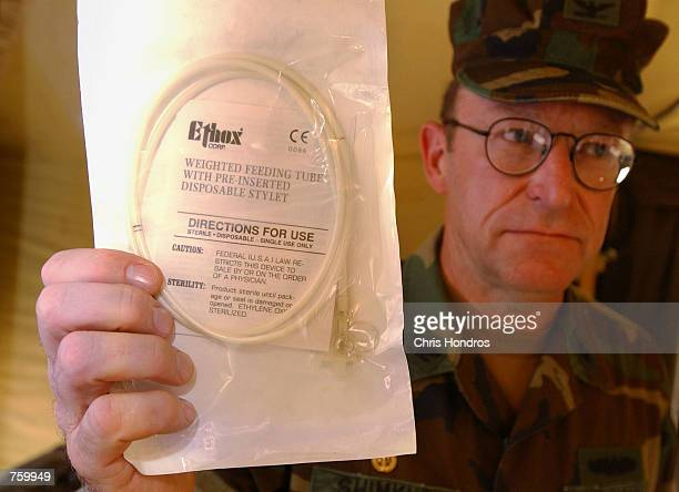 S Navy Captain Al Shimkus a member of the Navy Nurse Corps holds up a feeding tube March 28 2002 at the field Naval Hospital in Guantanamo Bay Cuba...
