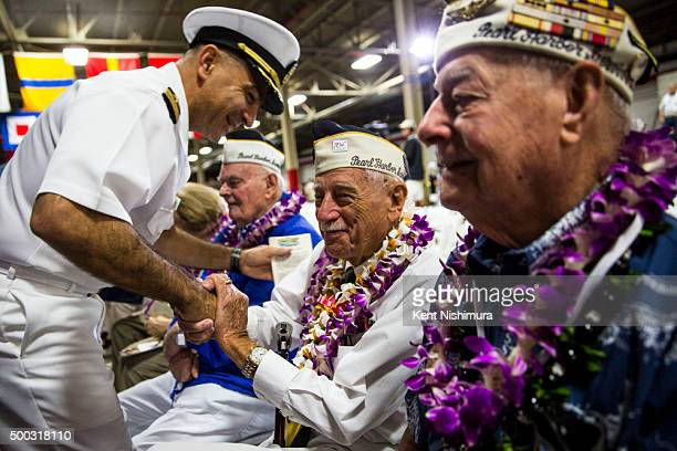 S Navy Captain Mark Manfredi greets Pearl Harbor Survivor Delton E Whaling before the start of a memorial service marking the 74th Anniversary of the...