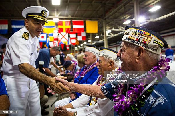 S Navy Captain Mark Manfredi greets USS Arizona Survivor Lou Conter before the start of a memorial service marking the 74th Anniversary of the attack...