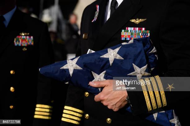 Navy Captain William Sherrod holds a flag from the USS Somerset to present to family members of the the victims at the Flight 93 National Memorial on...