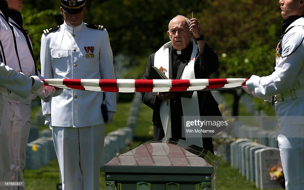 U.S. Navy Chaplain Jonathan Craig sprinkles holy water on a casket with the remains of four sailors missing since a helicopter crash during the Vietnam War in July 1967 during a full military honors burial service at Arlington National Cemetery May 2, 2013 in Arlington, Virginia. The remains of Lt. Dennis Peterson, Ensign Donald Frye, Aviation Antisubmarine Warfare Technician William Jackson and Aviation Antisubmarine Warfare Technician Donald McGrane were buried together during the service.