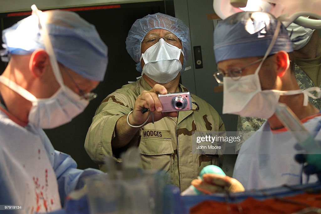 S. Navy Chaplain LCDR. Charles Hodges photographs as doctors perform brain surgery on an Afghan civilian on March 21, 2010 at the military hospital at Kandahar Airfield in southern Afghanistan. Chaplain Hodges is stationed at the hospital and also serves as the photographer for the medical unit. As part of his job, he also comforts wounded patients and counsels medical staff who often deal with a heavy caseload of patients, many suffering from traumatic injuries.