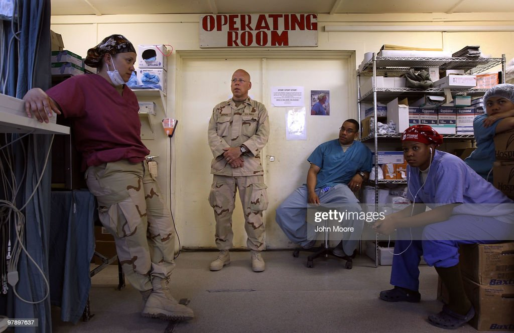 U.S. Navy Chaplain LCDR. Charles Hodges (C), waits with medical personnel as a patient is prepped from surgery March 20, 2010 at the military hospital at Kandahar Airfield in southern Afghanistan. Severely wounded American and other international soldiers are treated at the facility and then flown out for more advanced treatment outside of Afghanistan. Wounded and sick Afghan security forces are treated and later transferred to an Afghan-run hospital nearby. Chaplain Hodges, on fulltime duty at the hospital, comforts wounded patients and counsels medical staff who deal with a heavy caseload of patients, many suffering from traumatic war injuries.