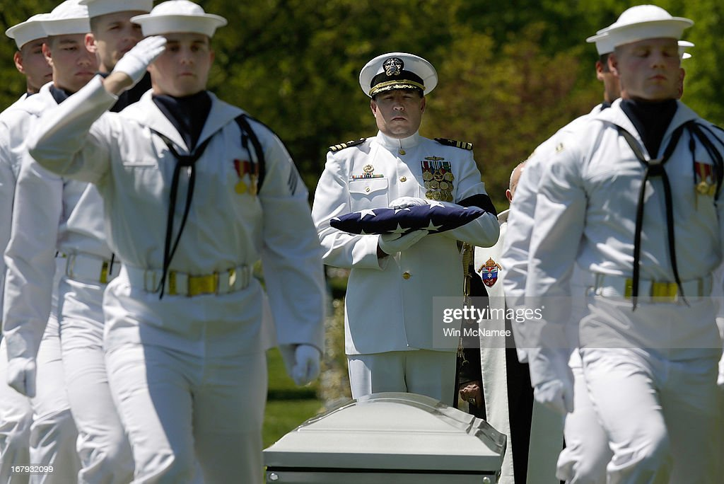 U.S. Navy Commander Nathaniel Strandquist holds an American flag that covered the casket with the remains of four sailors missing since a helicopter crash during the Vietnam War in July 1967 during a full military honors burial service at Arlington National Cemetery May 2, 2013 in Arlington, Virginia. The remains of Lt. Dennis Peterson, Ensign Donald Frye, Aviation Antisubmarine Warfare Technician William Jackson and Aviation Antisubmarine Warfare Technician Donald McGrane were buried together during the service.