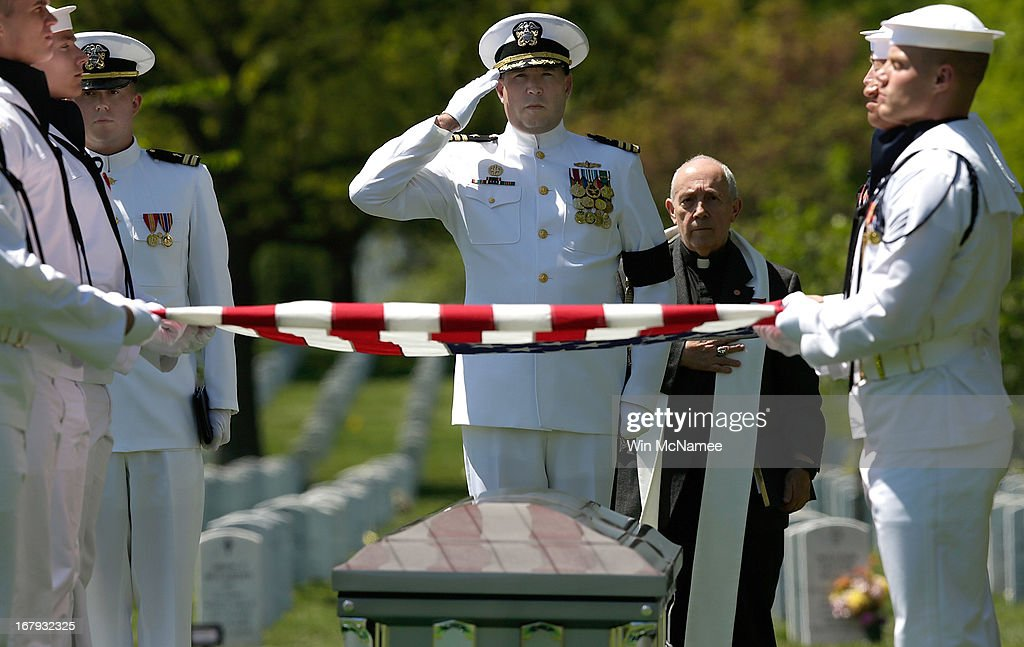 U.S. Navy Commander Nathaniel Strandquist salutes a casket with the remains of four sailors missing since a helicopter crash during the Vietnam War in July 1967 during a full military honors burial service at Arlington National Cemetery May 2, 2013 in Arlington, Virginia. The remains of Lt. Dennis Peterson, Ensign Donald Frye, Aviation Antisubmarine Warfare Technician William Jackson and Aviation Antisubmarine Warfare Technician Donald McGrane were buried together during the service. Also pictured is Navy Chaplain Jonathan Craig.