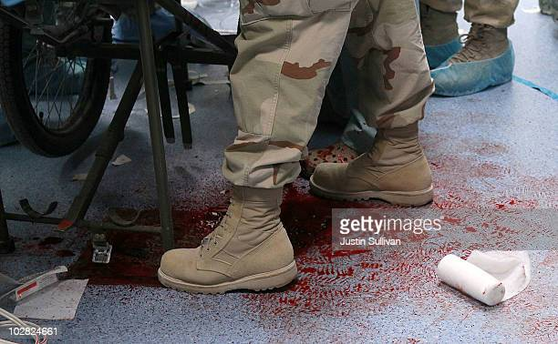 S Navy corpsman stands in a pool of blood while tending to a solider that was wounded by an IED blast at the Kandahar Role 3 Hospital July 12 2010 at...