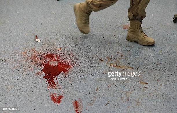 S Navy corpsman walks by a pool of blood on the floor from a solider that was wounded by an IED blast at the Kandahar Role 3 Hospital July 12 2010 at...