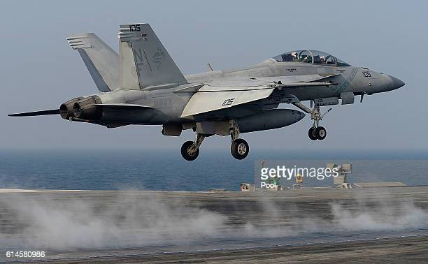S Navy crew members guide an F/A18 Super Hornet fighter takes off from the deck of USS Aircraft Carrier Ronald Reagan on October 14 2016 in Weat sea...