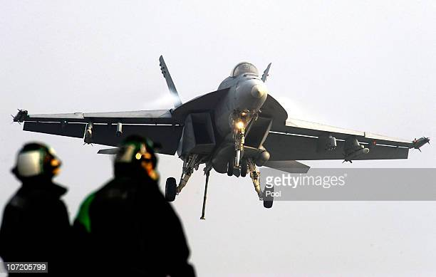 Navy crew members watch as a F18 Super Hornet strike fighter plane lands on the deck of USS George Washington during a joint US and South Korea...