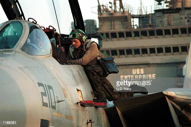 S Navy crewman prepares an F14A Tomcat for upcoming flight operations October 7 2001 on the flight deck of the USS Enterprise