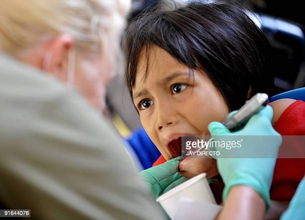 US Navy dentist Lieutenant Elisa Roth looks at the teeth of Filipino flood survivor Glendalyn Pisien at a medical mission in eastern Manila on...