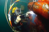 U.S. Navy Diver welds a repair patch on the submerged bow of the USS Ogden (LPD 5) while the ship was in port at Naval Base San Diego, California, January 4, 2007.