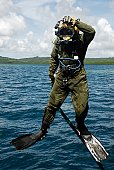 U.S. Navy Diver jumps off a dive station near the coast of Aimeliik, Republic of Palau, to do an excavation dive on February 26, 2007.  The Diver is temporarily assigned to the Joint POW/MIA Accountin