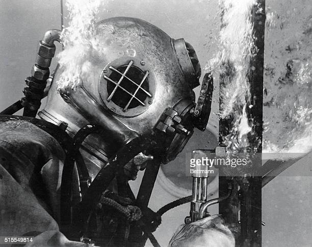 A Navy diver using special underwater cutting equipment is shown working his way through a ship resting at the ocean's bottom during a port operation...