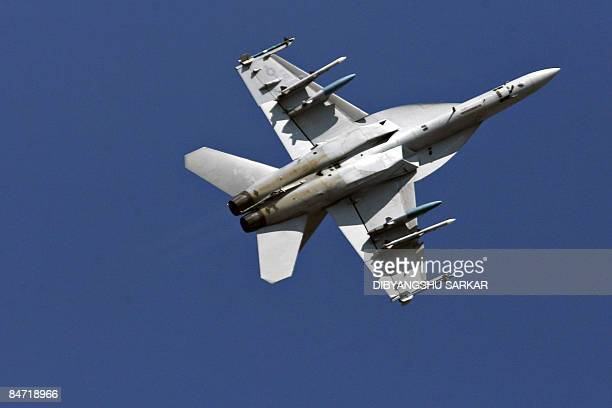 Navy F/A18F Super Hornet strike aircraft performs a roll during a flight demonstration at the Yelahanka Air Force Station in Bangalore on February 10...