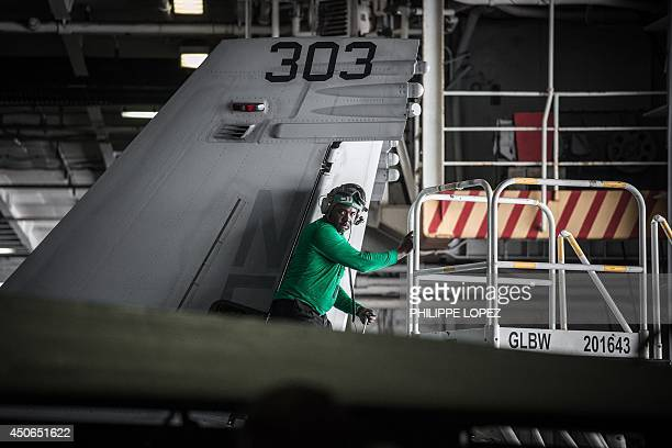 Navy 'green shirt' crew member works on the maintenance of a Boeing F/A18 Super Hornet multirole fighter aircraft in the hangar of the US...