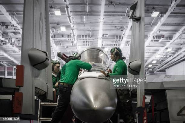US Navy 'green shirt' personnel work on the maintenance of a Boeing F/A18 Super Hornet multirole fighter in the hangar of the US nuclearpowered...