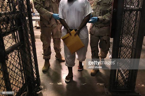 US Navy guards escort a detainee after a 'life skills' class held for prisoners at Camp 6 in the Guantanamo Bay detention center on March 30 2010 in...