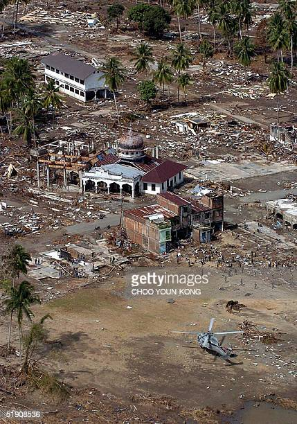 Navy helicopter Seahawk flies at a law altitude and releases food and water near damaged Muslim mosque in helpless village of Teunom near Meulabo 170...
