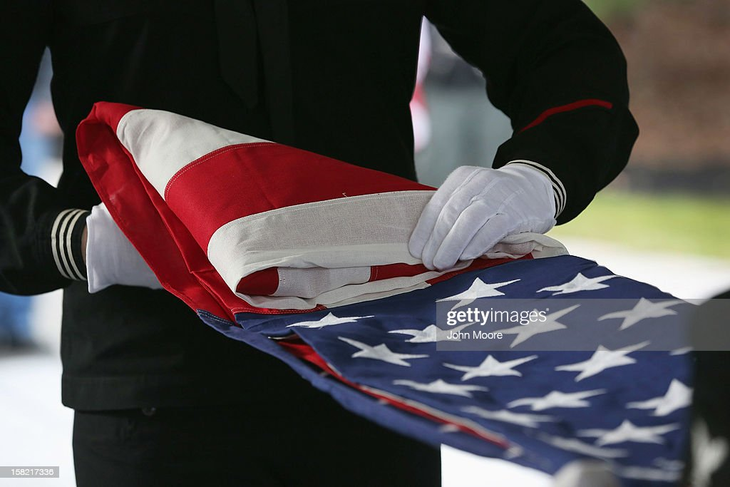 S. Navy honor guard folds an American flag after removing it from the casket of Hurricane Sandy victim David Maxwell, before his burial at the Calverton National Cemetery on December 11, 2012 near the Wading River hamlet of Long Island, New York. Maxwell, 66, was the last of Sandy's victims found on the Staten Island borough of New York City, when his body was discovered in his Midland Beach home 11 days after the storm. A Vietnam veteran, he was buried at the national cemetery, accompanied by honor guards from the Catholic War Veterans and the Patriot Guard Riders.
