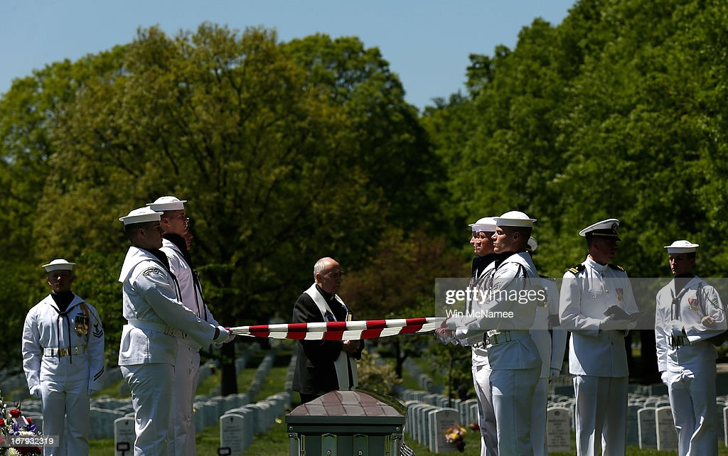 S. Navy honor guard team holds an American flag over a casket with the remains of four sailors missing since a helicopter crash during the Vietnam War in July 1967 during a full military honors burial service at Arlington National Cemetery May 2, 2013 in Arlington, Virginia. The remains of Lt. Dennis Peterson, Ensign Donald Frye, Aviation Antisubmarine Warfare Technician William Jackson and Aviation Antisubmarine Warfare Technician Donald McGrane were buried together during the service.