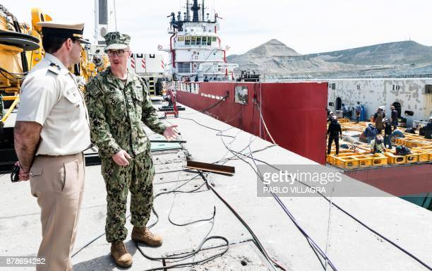 US Navy Karl Schonberd talks with a member of Prefectura Naval Argentina while workers weld the deck of the Sophie Siem vessel where members of the...