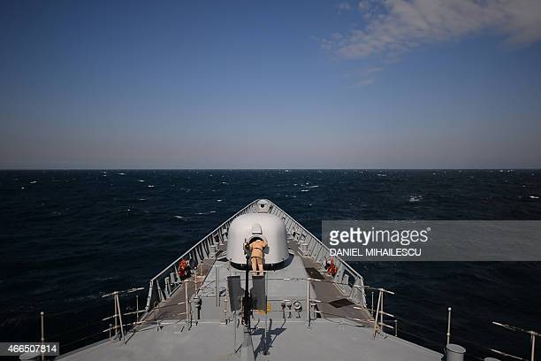 A navy man inspect a cannon of the Romanian frigate 'Regina Maria' during a military drill on the Black Sea 60km from Constanta city March 16 2015...