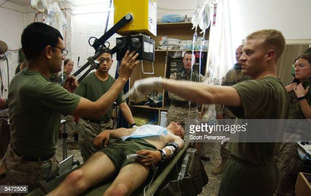 Navy medical corpsmen treat US Marines with bullet wounds inflicted during an ambush by Iraqi insurgents east of the encircled city of Fallujah Iraq...