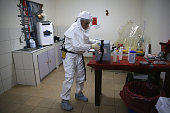 S Navy microbiologist Lt Jimmy Regeimbal handles a vaccine box with blood samples while testing for Ebola at the US Navy mobile laboratory on October...