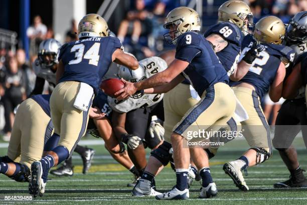 Navy Midshipmen quarterback Zach Abey hands the ball off to fullback Mike Martin on October 21 at Navy Marine Corps Memorial Stadium in Annapolis MD...