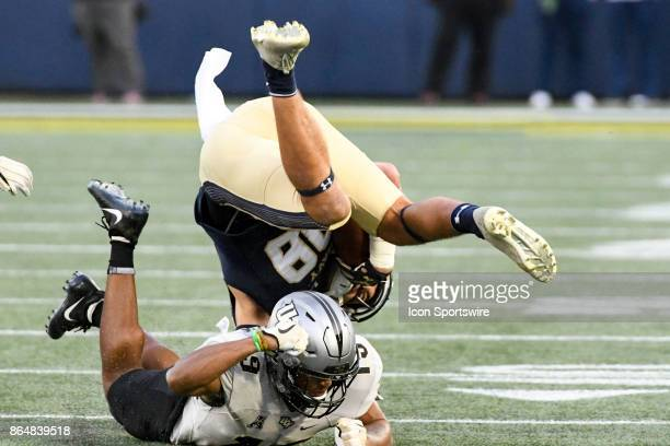 Navy Midshipmen wide receiver Tyler Carmona makes a catch and sis updended by UCF Knights defensive back Mike Hughes on October 21 at Navy Marine...