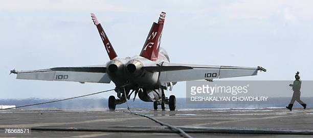 Navy officer signals a fighter plane during landing on the US supercarrier USS Kitty Hawk in the Bay of Bengal during the Malabar exercise 07...