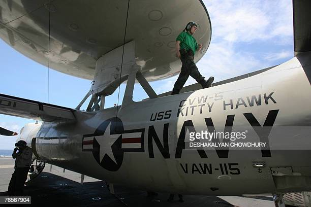 Navy officer walks along the body of a fighter plane parked on the US supercarrier Kitty Hawk in the Bay of Bengal during the Malabar exercise 07...