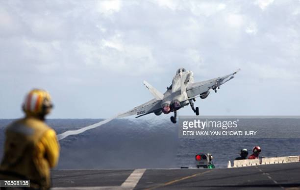 A US navy officer watches as a fighter plane shoots out from the US supercarrier USS Kitty Hawk in the Bay of Bengal during the Malabar exercise 07...