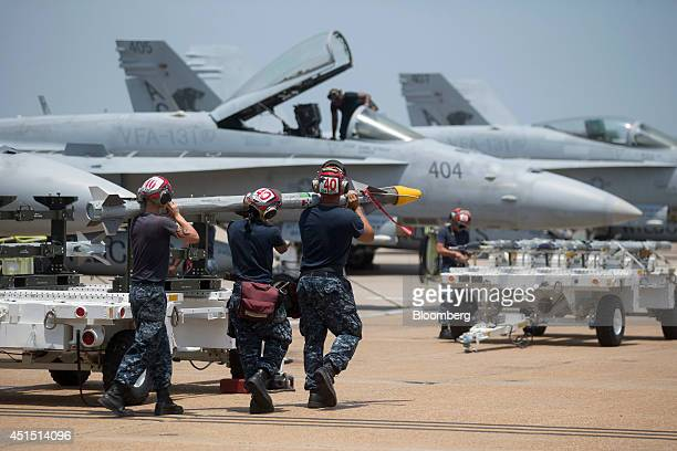 US Navy ordnancemen from the Strike Fighter Squadron 'Wildcats' dearm an F/A18C aircraft on the flight line at the Naval Air Station Oceana in...