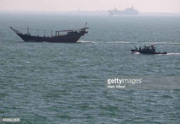 Navy patrol boat follows a boat that passed near the USS Ponce where US Secretary of Defense Chuck Hagel was taking a tour on December 6 2013 in...