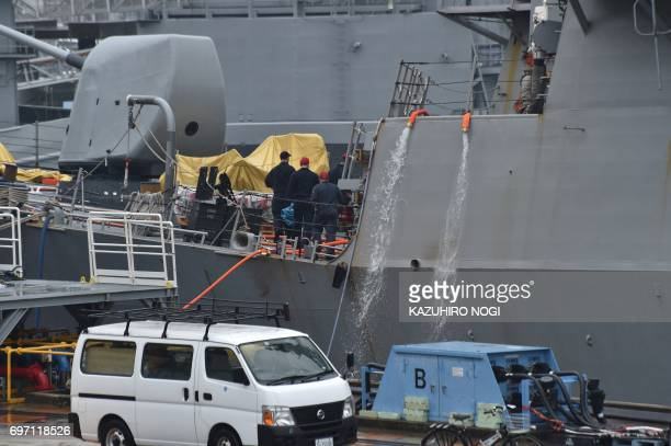 US navy personel work on the guided missile destroyer USS Fitzgerald at its mother port in Yokosuka southwest of Tokyo on June 18 2017 A number of...