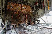US Navy personnel load relief goods to be transported to regions affected by Typhoon Bopha aboard the Marine Corps KC130J Hercules millitary aircraft...